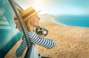 Young woman enjoying drive along coastline.