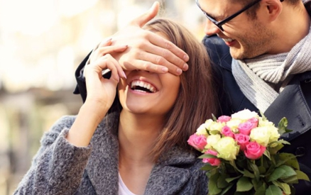 Young romantic couple, man surprising woman with flowers