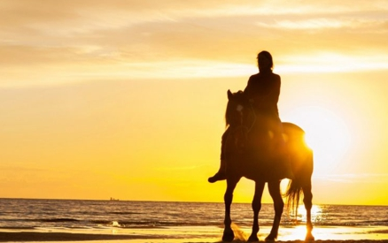 Man horseback riding along the beach at sunset