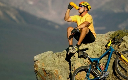 Bicyclist resting on mountain side enjoying view