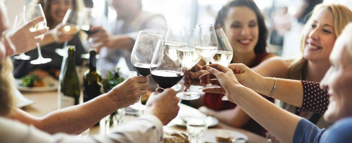 group of people of different ages around a restaurant dining table clinking wine glasses